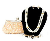 Fashionable handbag and pearl jewelry on white background. — Stock Photo