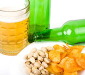 Potato chips and pistachios with beer on white — Stock Photo