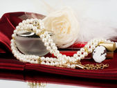 Pearl jewelry on red background — Stock Photo