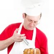 Male cook in uniform and hat with cake chocolate cake — Stock Photo #9986215
