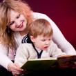 Mother and baby boy reading book — Stock Photo #9986543