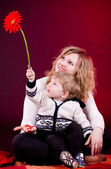 Portrait of mother and young baby boy with red flower — Stockfoto