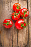 Fresh tomatoes on vintage wooden table — Stock Photo