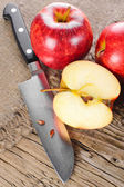 Ripe apple fruits and knife at old wooden table with canvas — Stock Photo