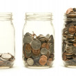 Three glass jars holding coins — Stock Photo