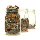 Three glass jars filled with American coins — Stock Photo