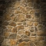Brown masonry rock wall lit dramatically — Stock Photo #9633371
