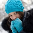 Young girl warms frozen hands your breath — Stock Photo