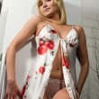 Sexy blonde in a negligee on the background of the refrigerator — Stock Photo