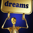 Foto Stock: Golden skeleton holding the sign