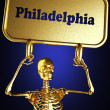 Golden skeleton holding sign — Stock Photo #10385507