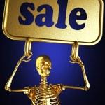 Golden skeleton holding the sign — Stock Photo #10397819