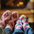 Young romantic couple sitting on sofa in front of fireplace at h — Stock Photo