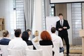 Young business man giving a presentation on conference — Stock Photo