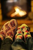 Young romantic couple relax on sofa in front of fireplace at hom — Stok fotoğraf