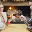 Young romantic couple sitting and relaxing in front of fireplace at home - Stok fotoraf