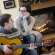 Young romantic couple sitting and relaxing in front of fireplace at home — Stock Photo #10250624