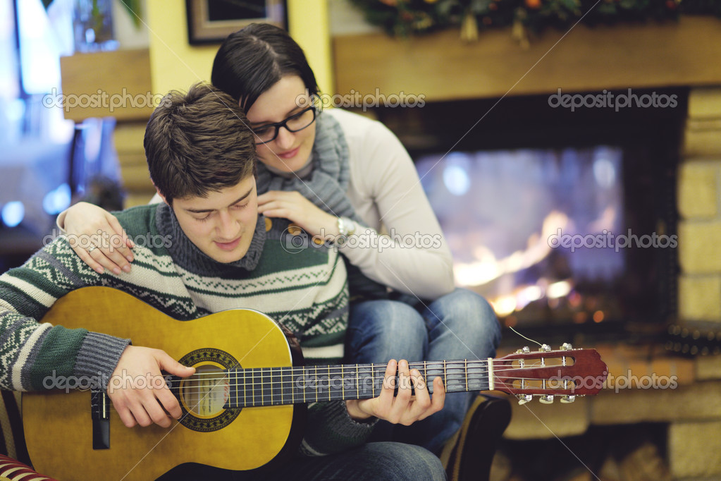 Happy Young romantic couple and relaxing sofa in front of fireplace at winter season in home — Stock Photo #10250629