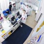 Pharmacist suggesting medical drug to buyer in pharmacy drugstore — Stock Photo #10575012
