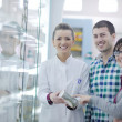 Pharmacist suggesting medical drug to buyer in pharmacy drugstore - Stok fotoraf