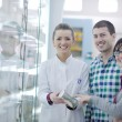 Pharmacist suggesting medical drug to buyer in pharmacy drugstore - Stockfoto