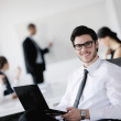 Portrait of a handsome young business man with colleagues in background — Stock Photo #10575441