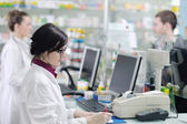 Pharmacist suggesting medical drug to buyer in pharmacy drugstore — Foto de Stock