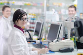 Pharmacist suggesting medical drug to buyer in pharmacy drugstore — Stock Photo