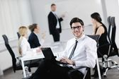 Portrait of a handsome young business man with colleagues in background — Stock Photo