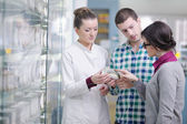 Pharmacist suggesting medical drug to buyer in pharmacy drugstore — Stock Photo