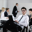 Handsome young business man with colleagues in background — Stock Photo #10652805