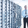Businessman with laptop in network server room — Stock Photo