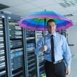 Stock Photo: Businessman hold umbrella in server room