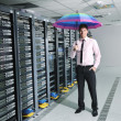 Businessman hold umbrella in server room - Stock Photo