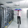 Businessman hold umbrella in server room — Stock Photo #8338397