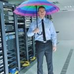 Businessman hold umbrella in server room — Stock Photo #8338519