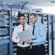 It enineers in network server room - Stock Photo