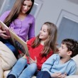 Young mom play with their kids at home and reading book - Foto Stock