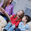 Young mom play with their kids at home and reading book — ストック写真