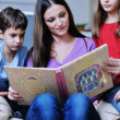 Young mom play with their kids at home and reading book — Stock Photo #8491526