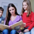 Young mom play with their kids at home and reading book — Stock Photo #8491539