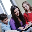 Stock Photo: Young mom play with their kids at home and reading book