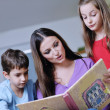 Young mom play with their kids at home and reading book — Stock Photo #8491610