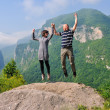 Happy young couple jumping in the air — Stock Photo