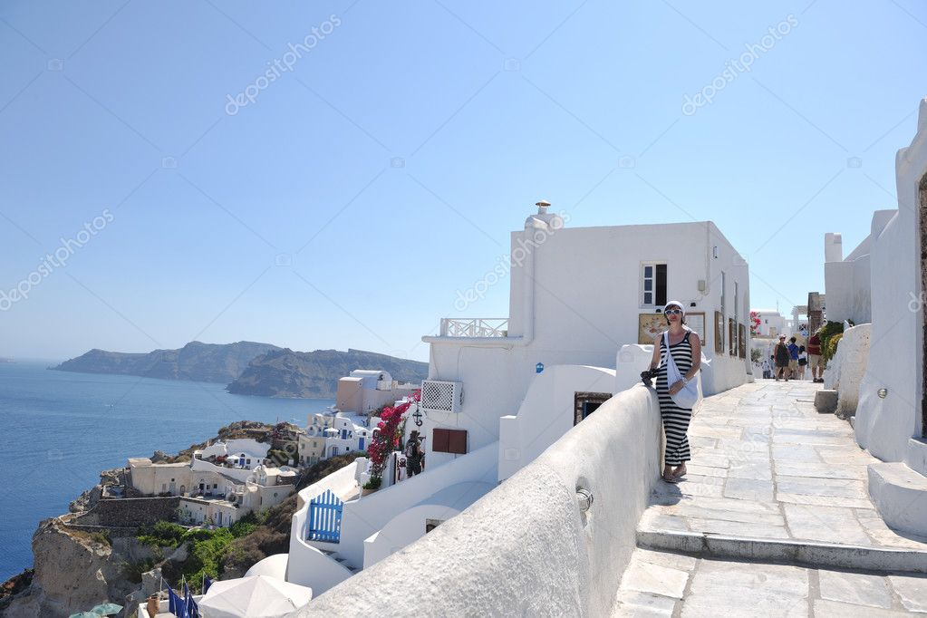 Beautiful young Greek woman in fashion clothes have fun at n the streets of Oia, Santorini, Greece — Stock Photo #8491761