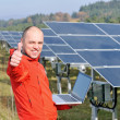 Engineer using laptop at solar panels plant field — 图库照片