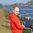 Engineer using laptop at solar panels plant field — ストック写真