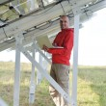 Engineer using laptop at solar panels plant field — Stock Photo