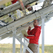Engineer using laptop at solar panels plant field — Stock Photo #8993745