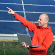 Engineer using laptop at solar panels plant field — Stok fotoğraf